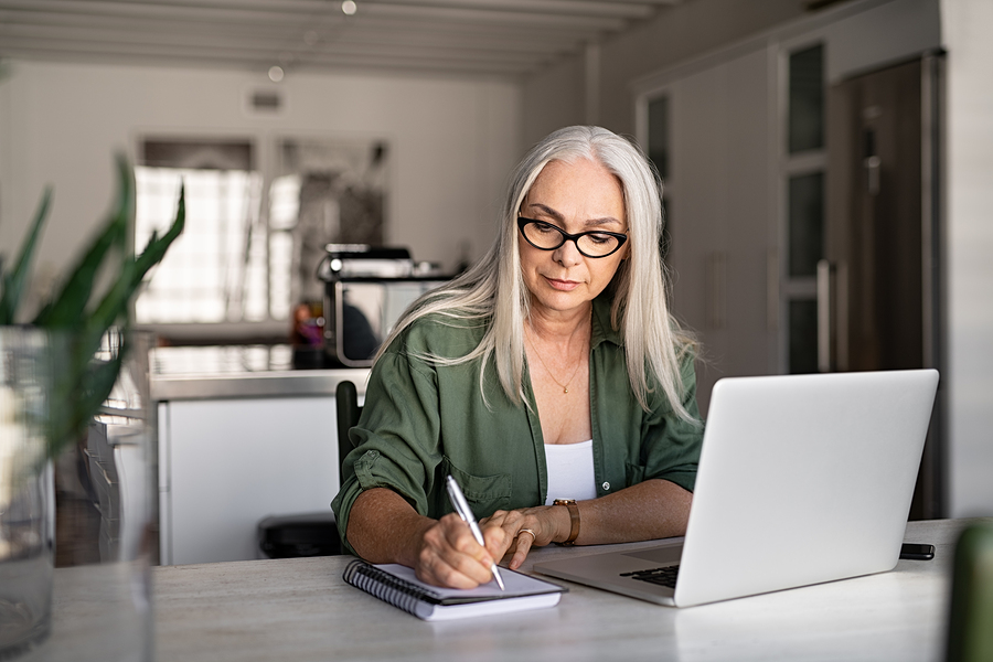 Senior woman taking inventory of digital assets on notebook in front of laptop