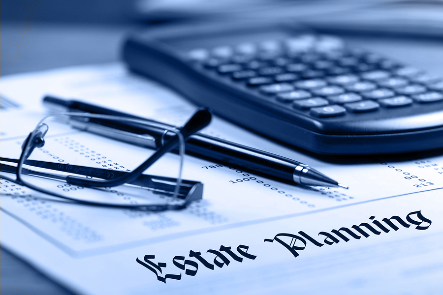 Estate planning documents outlining how estate taxes work underneath pair of glasses and a calculator